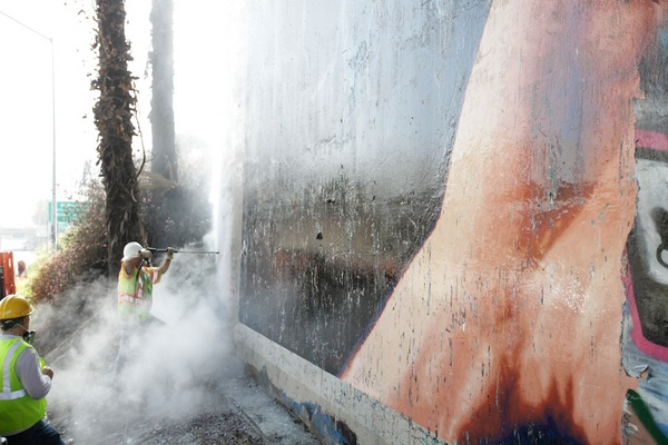 Graffiti being cleaned away from Jim Morphesis Monument I Photo: Gil Ortiz Photos