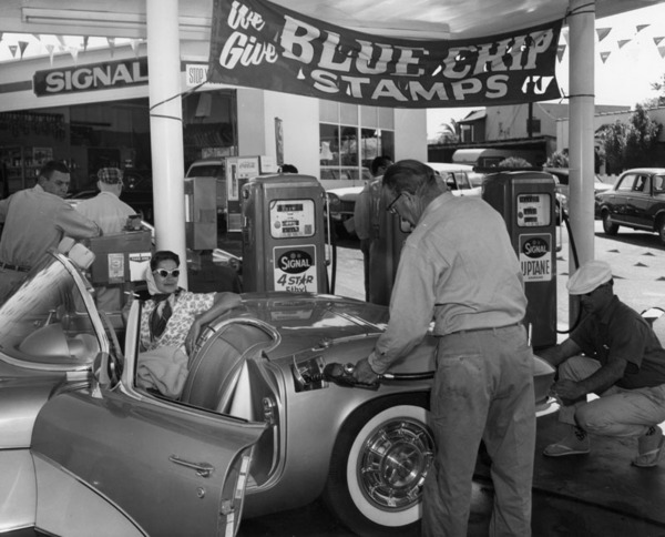 Man pumps gas into his sports convertible at the Signal service station ca. 1960 | Courtesy of the Los Angeles Public Library