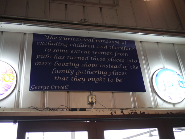 A sign with words from George Orwell that call for the pub as a family gathering place | Photo by George Villanueva