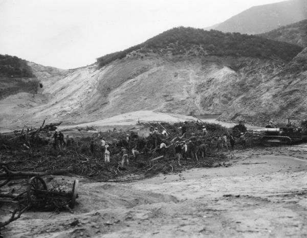 This post-failure photograph shows men working in a field of broken trees, wagons and other debris attempting to clear it away | Security Pacific National Bank Collection, Courtesy of the Los Angeles Public Library