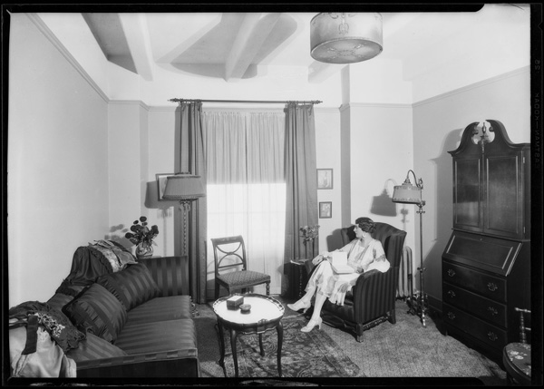 Woman lounging inside one of the guest rooms | Dick Whittington Studio Collection, USC Digital Library