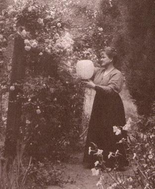 Olive Percival hangs lanterns in her garden | Photo from The Children's Garden Book