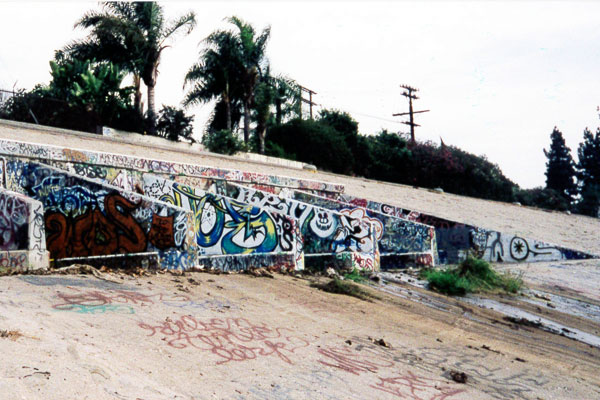 Concrete flood-control structures also serve as canvases for young and veteran graffiti artists. 1999 I Photo by Juan Devis