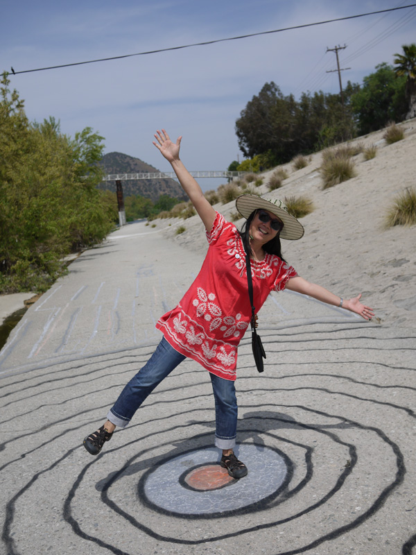 Atwater resident Angela Gee playfully poses on top of an artistic vortex creation along the riverbank | Photo by George Villanueva