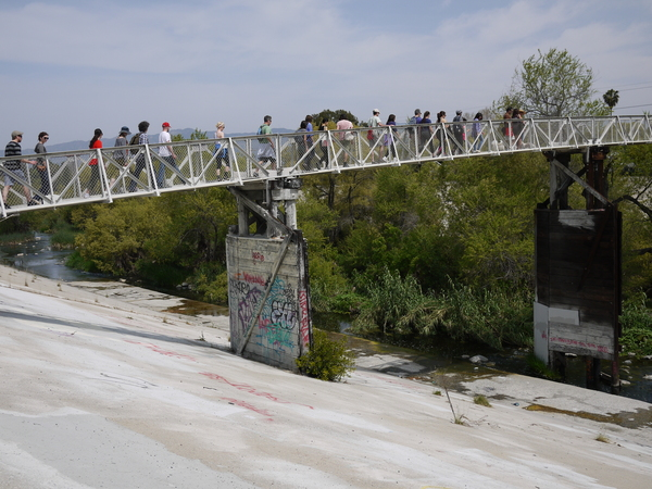 Walkers cross the pedestrian bridge over the river | Photo by George Villanueva