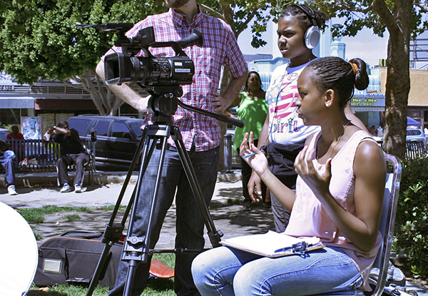 Anbiya asks questions as Joy monitors the camera and audio