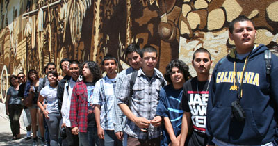 "Students stand next to the ""The History of Highland Park"" mural"