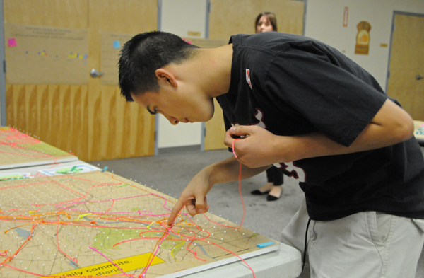 A student finds his neighborhood on a map. <em>Photo by Justin Cram</em>