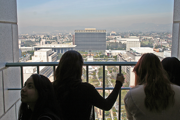 A group of students look out towards Grand Park and the Music Center. The Hollywood sign is visible in the top right through the mid-day haze