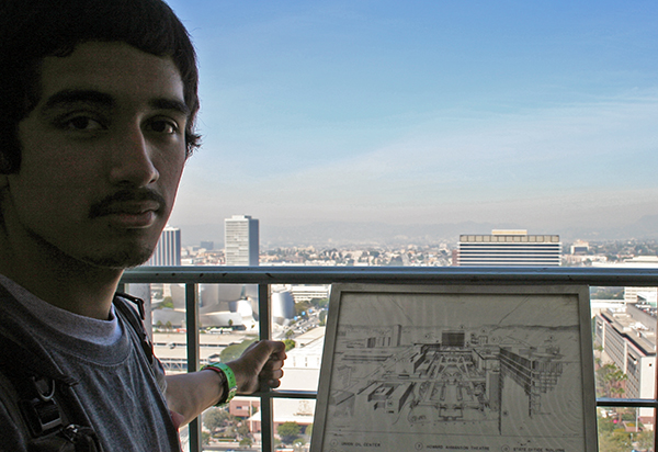 A student stands next to an old city guide that contrasts sharply with the current view of Los Angeles
