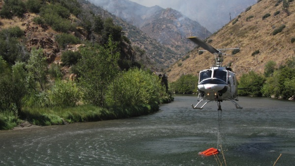 A helicopter retrieves water in the Kern River to fight a fire south of Giant Sequoia National Monument in 2011 | Photo: Zach Behrens/KCET