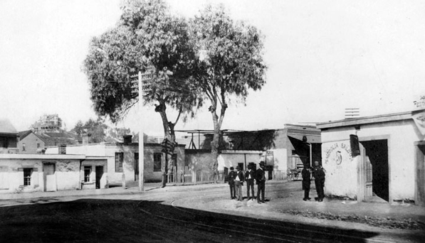 Men stand outside a Sonoratown saloon at Bellevue and Upper Main (now Spring), circa 1888. In the distance, the mansion of retail magnate J.W. Robinson sits atop Fort Moore Hill. Courtesy of the Los Angeles Public Library Photograph Collection.