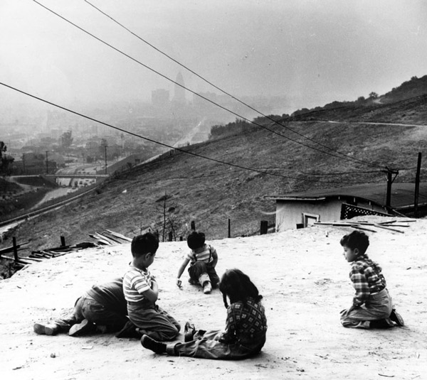 Children play on a hilltop near Chavez Ravine with a smoggy Los Angeles skyline visible in the background. Photo by Don Normark, courtesy of the Photo Collection, Los Angeles Public Library.