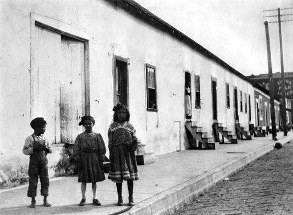 Three girls stand in front of the Florentina Ybarra adobe at the current intersection of Spring and Ord, circa 1890s. Courtesy of the Los Angeles Public Library Photograph Collection.