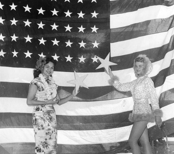 Women representing the newly-admitted states of Hawaii and Alaska hold up stars to the old 48-star U.S. flag at the Rose Bowl's 1959 July 4 celebration. Courtesy of the Hollywood Citizen News/Valley Times Collection, Los Angeles Public Library.