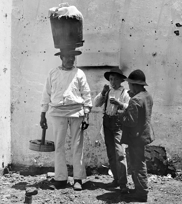 Two boys buy ice cream from vendor Nicolas Martinez, who walked the streets of Sonoratown with his wares on his head. Courtesy of the Title Insurance and Trust / C.C. Pierce Photography Collection, USC Libraries.