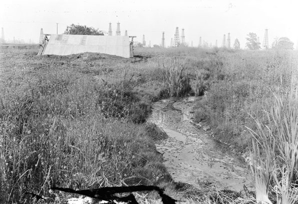 The La Brea Tar Pits in 1927, with oil derricks visible in the background. Courtesy of the California Historical Society Collection, USC Libraries.