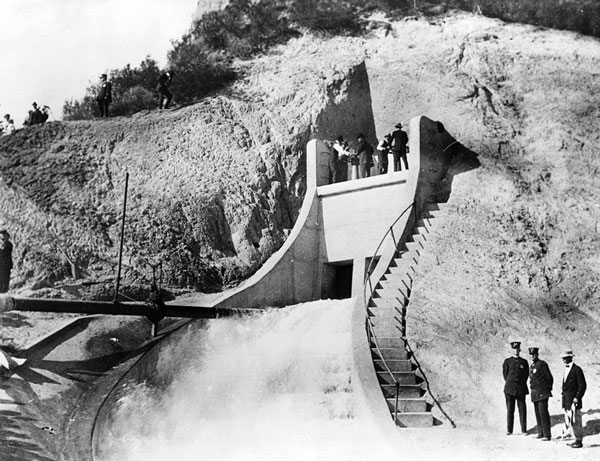 November 5, 1913 opening of the Los Angeles Aqueduct. Project engineer William Mulholland is at one of the wheels, opening the Sylmar Gates for the first time. Courtesy of the Title Insurance and Trust / C.C. Pierce Photography Collection, USC Libraries.