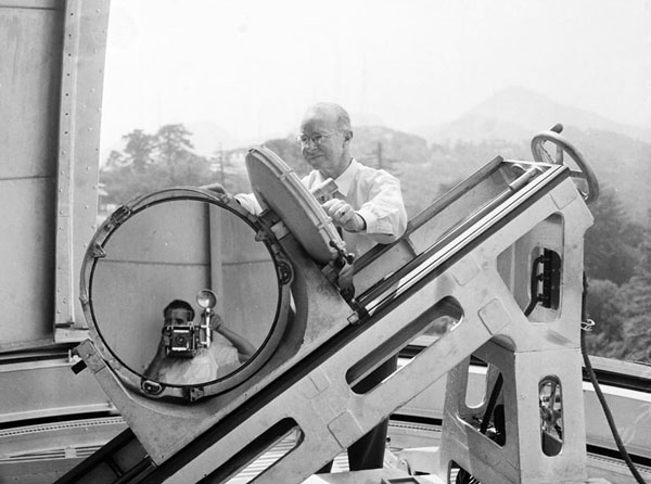 Mount Wilson telescope operator Joseph Hickox polishes a mirror while an Examiner photographer takes a self-portrait. 1955 photo courtesy of the Los Angeles Examiner Collection, USC Libraries.