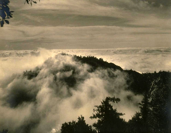The inversion layer usually keeps fog and other airborne obstructions below Mount Wilson's telescopes. Courtesy of the William C. Barry Collection of Los Angeles Area Photography, Bancroft Library, UC Berkeley.