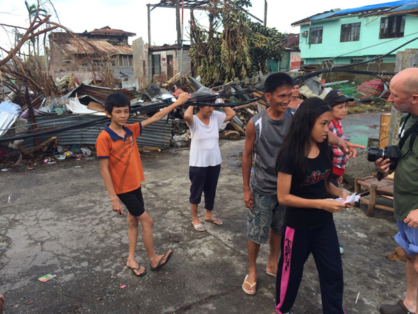 Survivors of Typhoon Haiyan in Tanauan, Leyte, Philippines walk amidst the rubble days after the storm.