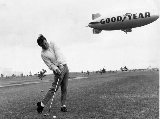 Golfer Ron Hollis takes a shot in 1969, with the Goodyear blimp hovering in the background. From the California State University Dominguez Hills Photograph Collection.<br />