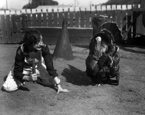 A woman mock-threatens a turkey with her hatchet. Courtesy of the Security Pacific National Bank Collection, Los Angeles Public Library.
