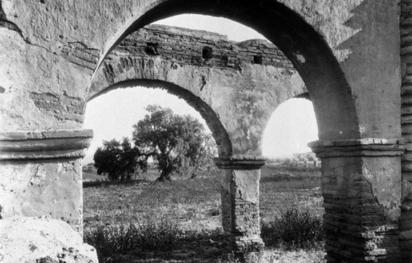 A pepper tree as seen through the ruins of Mission San Luis Rey in San Diego County. Courtesy of the USC Libraries - California Historical Society Collection.