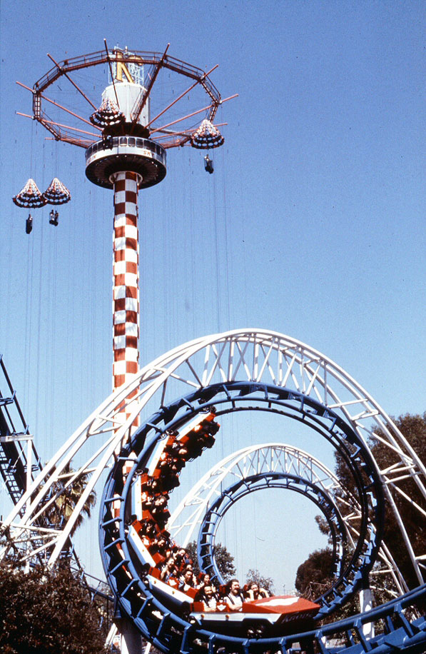 In the 1970s, roller coasters made their first appearance inside Knott's Berry Farm. This photo from circa 1980 shows the Corkscrew roller coaster in front of the Parachute Sky Jump ride. Courtesy of the Orange County Archives.
