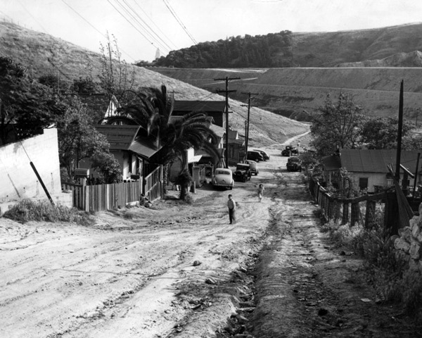 Two children walk up a dirt road in the Chavez Ravine area in 1950. Photo Leonard Nadel, courtesy of the Southern California Library for Social Studies & Research.