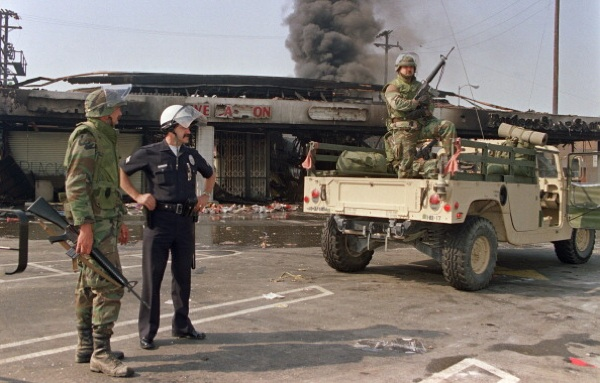 National Guardsmen and a police officer take up security positions in front of a burned and looted shopping center on May 1st, 1992 in central Los Angeles. | Photo: HAL GARB/AFP/Getty Images)