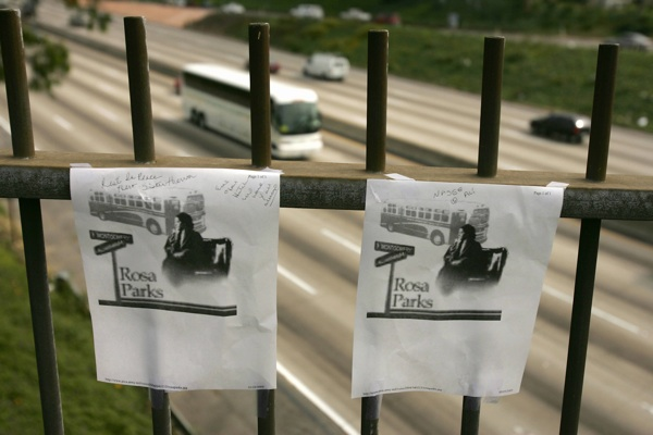 Photos of Rosa Parks hang at a highway overpass in Los Angeles named for the American civil rights icon after a tribute by black community leaders on October 25, 2005. | Photo: ROBYN BECK/AFP/Getty Images