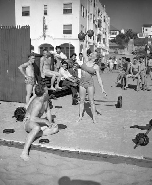 Bodybuilder Abbey Stockton lifts a dumbbell as a crowd looks on at Muscle Beach, 1947.