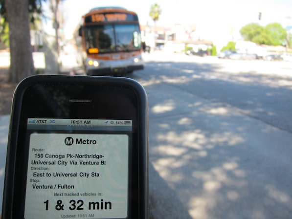 A Metro bus arrives as NextBus technology tells a cell phone user that buses will be arriving in 1 and 32 minutes | Photo by Zach Behrens/KCET