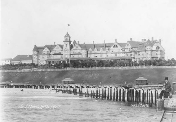 A man sits on a pier in front of the Redondo Hotel on Redondo Beach, 1894. From the South Bay Photograph Collection