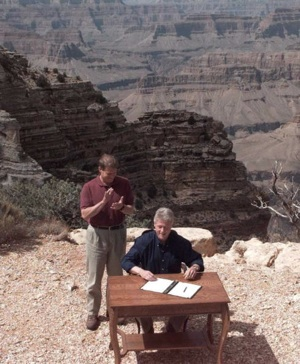 Former President Bill Clinton signs an order creating Grand Staircase-Escalante National Monument with the Grand Canyon as his backdrop | Photo: LUKE FRAZZA/AFP/Getty Images