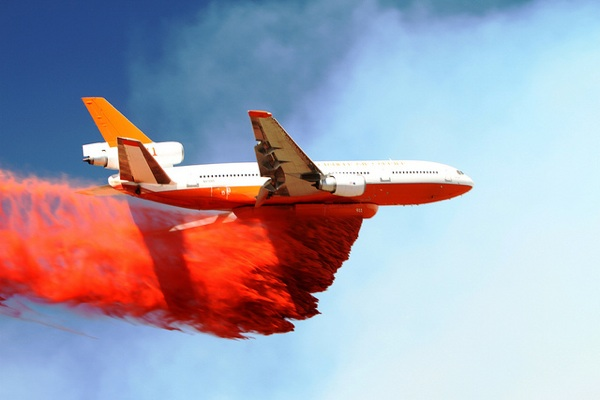 The DC-10 Very Large Air Tanker (VLAT) drops fire retardant to reinforce the line above Greer, AZ