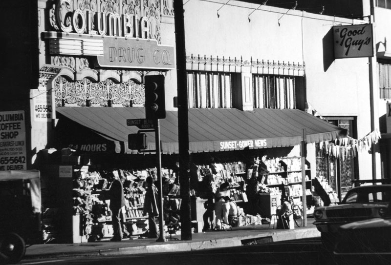 Drugstore cowboys awaited movieland employment at the corner of Sunset and Gower, where the manager of the Columbia Drug Co. let would-be extras use the phone booth. By the time of this photograph, in 1977, Sunset-Gower news had set up shop.
