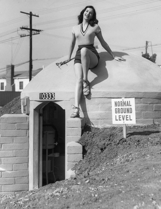 Mary Lou Miner, in summer sportswear, poses on top of a concrete-block bomb shelter. Apr. 7, 1951. | LAPL