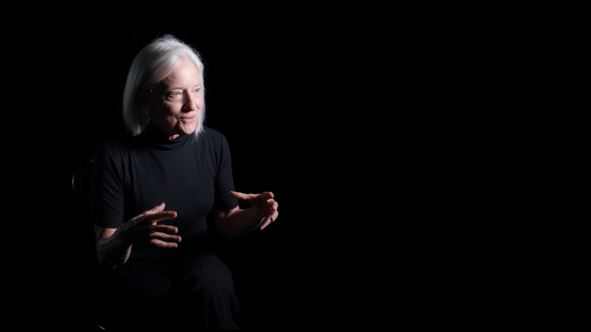Ann Carlson sits in front of a black background. | Courtesy of UCLA