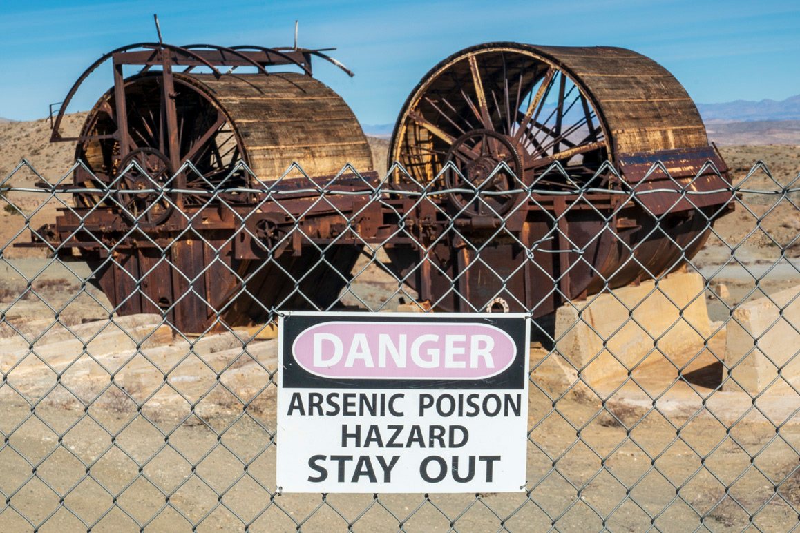 Abandoned mill machinery with an arsenic hazard warning sign shown in the foreground. | Kim Stringfellow.