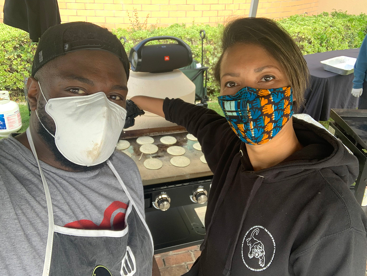 Two East Side Rider members wearing face masks make meals | Courtesy of East Side Riders