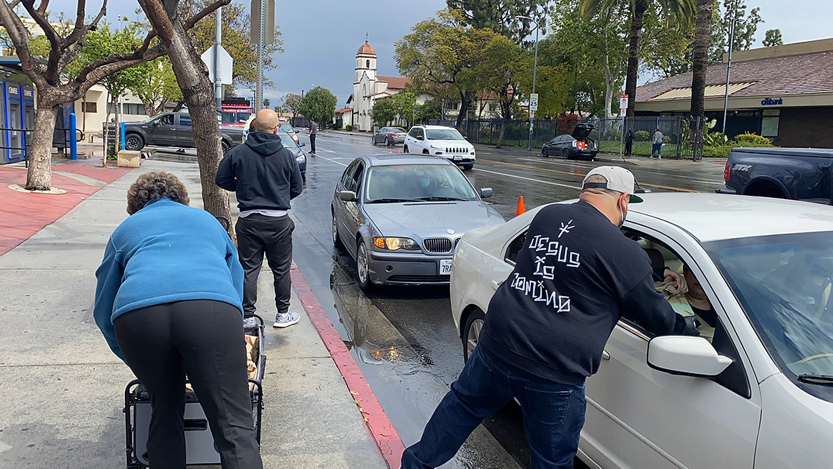 East Side Riders Bike Club members pass food to those waiting in cars | Courtesy of East Side Riders