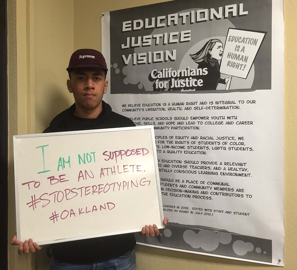 """A young man hold out a sign that says """"I'm not supposed to be an athlete"""" as part of the """"Flip the Frame"""" campaign to challenge the damaging assumptions imposed on Black and Brown youth. 