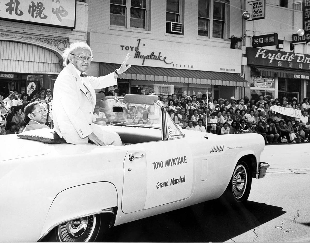Toyo Miyatake waving the crowd while Archie Miyatake drives during the 1979 Nisei Week Parade | Courtesy of Toyo Miyatake Studio