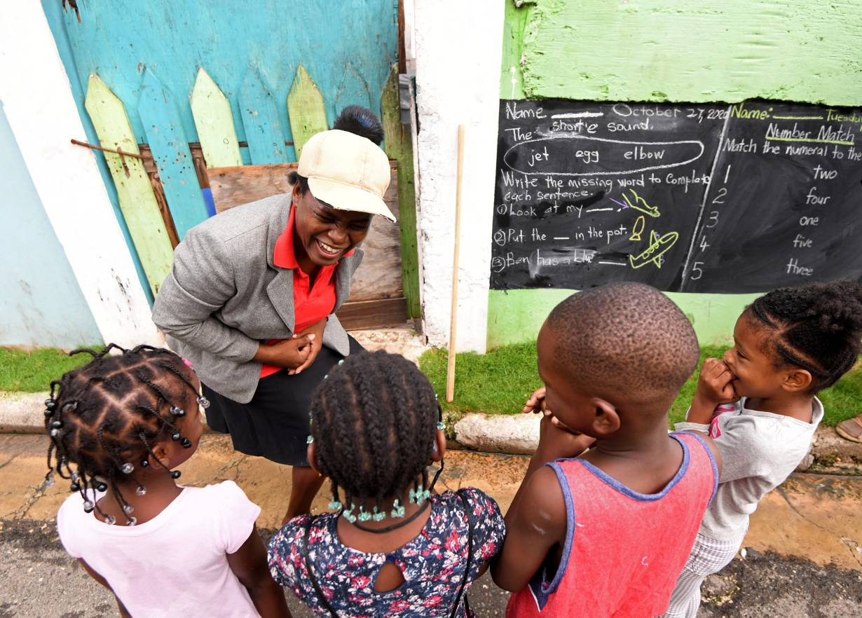 Educator Taneka Mckoy Phipps teaches a lesson with a blackboard painted on a wall, in a low-income neighborhood, during the coronavirus disease (COVID-19) outbreak in Kingston, Jamaica October 27, 2020. October 27, 2020.   REUTERS/Gladstone Taylor