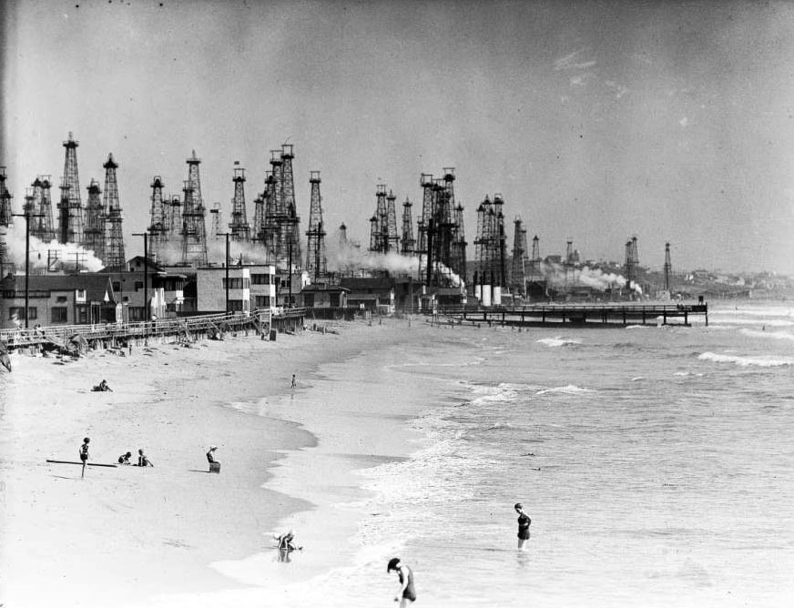 Beachgoers frolic beneath the gaze of oil derricks in Venice. Courtesy of the USC Libraries - California Historical Society Collection.