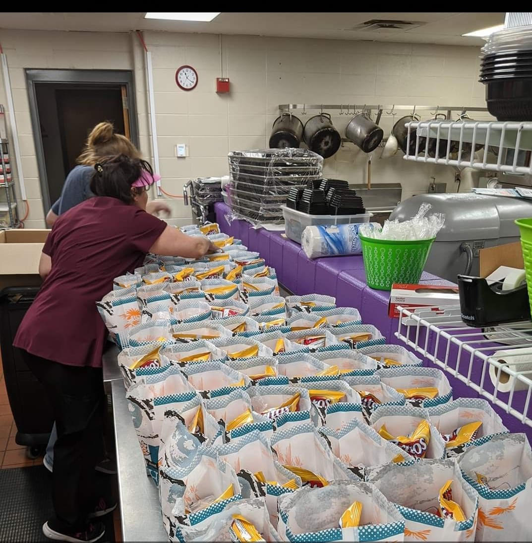 School food service workers packing bags in the school kitchen for meal distribution | Cindy Watkins Hardin in Harrison County, Kentucky
