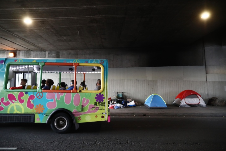 A tour bus passes a homeless encampment located beneath an overpass on June 5, 2019 in Los Angeles. | Mario Tama/Getty Images via LAist