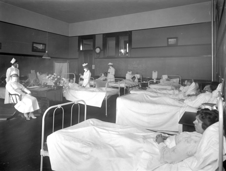 Pasadena, approximately 1919: Patients rest in hospital beds while nurses wearing breathing masks tend to them. | Harold A. Parker/Huntington Digital Library